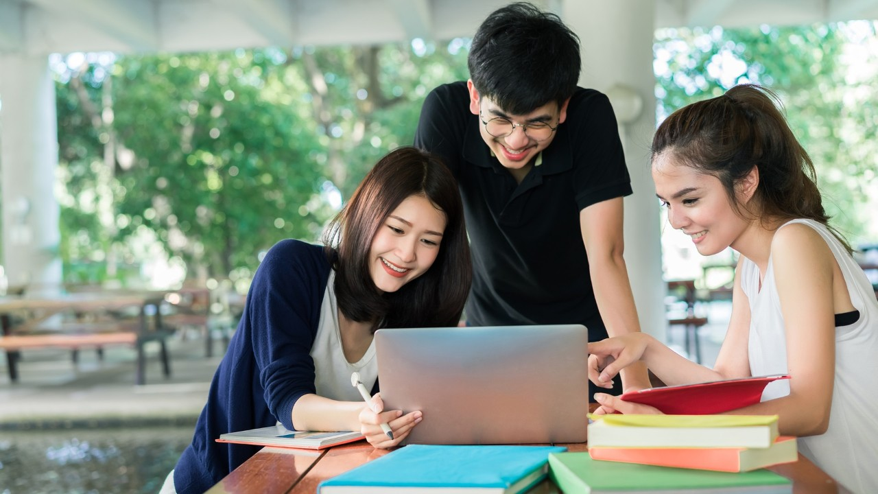Three students discuss issues in front of a laptop; image used for guidance with Premier Next Generation