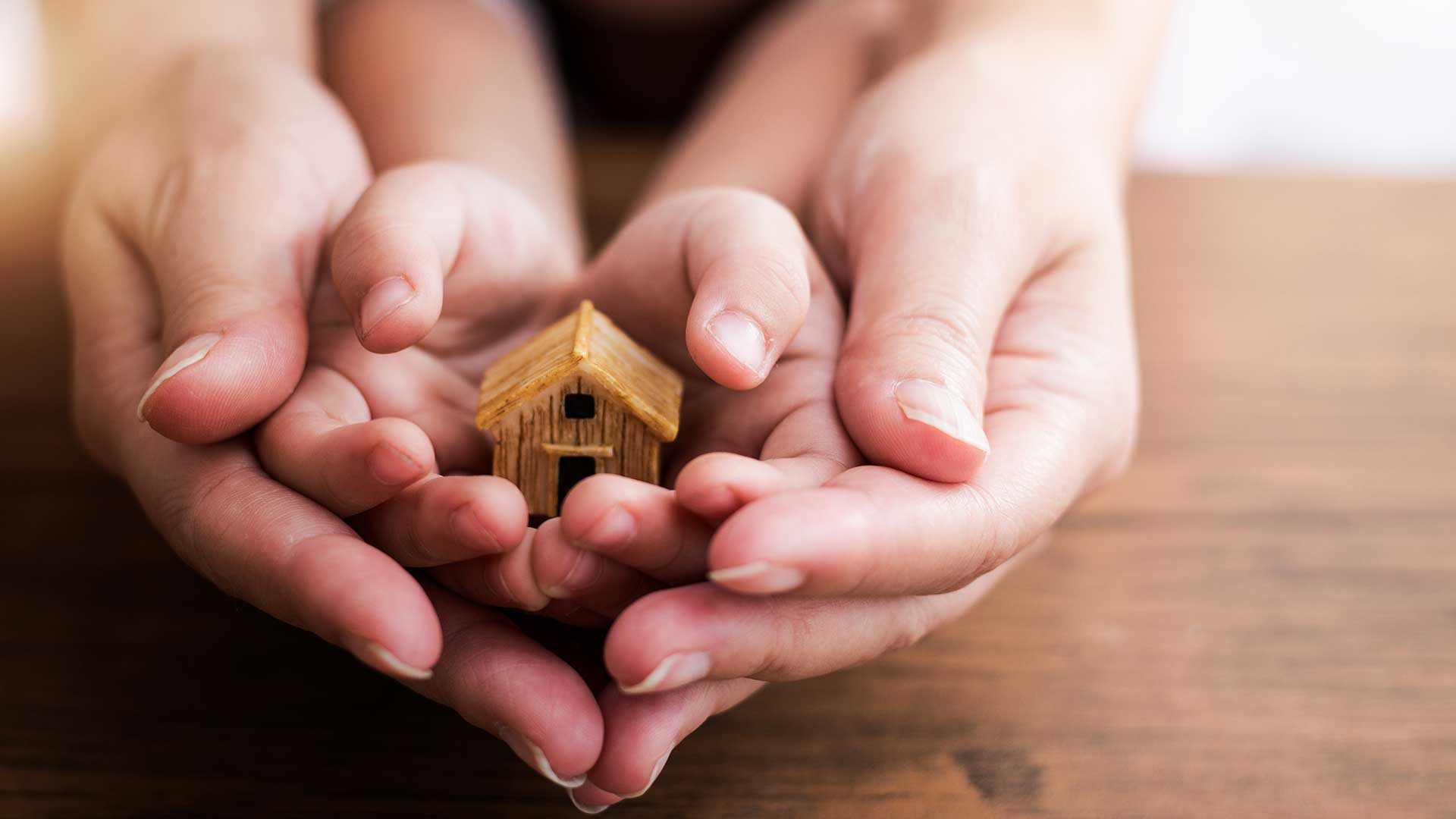holding a house model; the image used for wealth education
