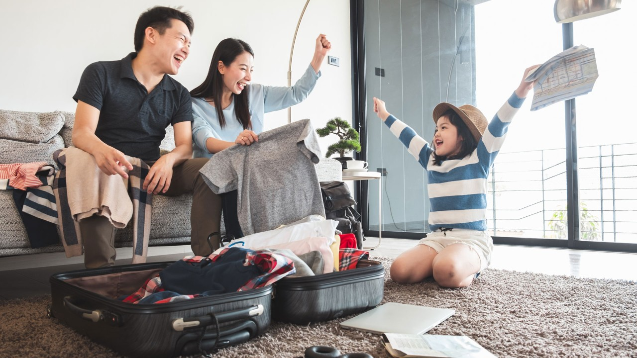 Parents and daughter packing up luggage, ready to travel